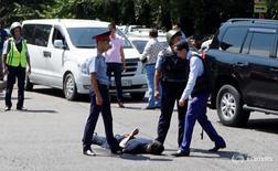 Полицейские задерживают человека после стрельбы в центре Алма-Аты 18 июля 2016 года. Жертвами стрельбы в центре крупнейшего города Казахстана Алма-Аты стали несколько сотрудников полиции, сообщило МВД страны. REUTERS/Pavel Mikheyev