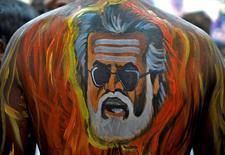 "A fan with his body painted with an image of actor Rajinikanth is pictured outside a movie theatre showcasing the Tamil film ""Kabali"" in Bengaluru, India, July 22, 2016. REUTERS/Abhishek N. Chinnappa"