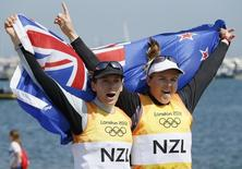 New Zealand's Jo Aleh (L) and Olivia Powrie celebrate with their national flag as they arrive in the harbour after winning gold in the women's 470 sailing class at the London 2012 Olympic Games in Weymouth and Portland, southern England, August 10, 2012. REUTERS/Pascal Lauener