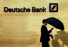 A man walks past Deutsche Bank offices in London December 5, 2013. REUTERS/Luke MacGregor/File Photo