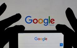 A woman holds her smart phone which displays the Google home page, in this picture illustration taken February 24, 2016.   REUTERS/Eric Gaillard/Illustration/Files