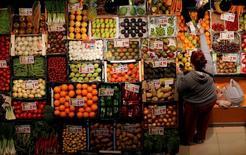 Los precios en España frenaron ligeramente su tendencia negativa en julio, según datos publicados el viernes por el Instituto Nacional de Estadística. En la imagen, una mujer compra frutas y verduras en un mercado de Sevilla, el 7 de marzo de 2016. REUTERS/Marcelo del Pozo
