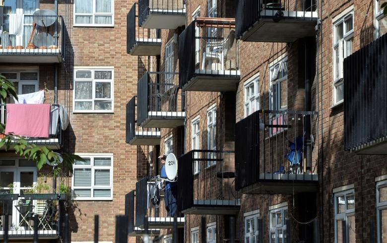 A man stands on a balcony in a residential high rise block of flats in Notting Hill in central London October 8, 2013.   REUTERS/Toby Melville