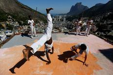 Members of the Acorda Capoeira (Awaken Capoeira) group perform on a rooftop in the Rocinha favela in Rio de Janeiro, Brazil, July 24, 2016. REUTERS/Bruno Kelly