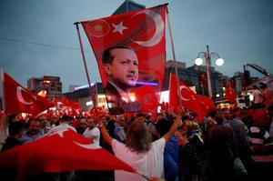 A supporter holds a flag depicting Turkish President Tayyip Erdogan during...
