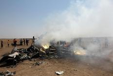 Повстанцы осматривают обломки сбитого российского вертолета в провинции Идлиб. 1 августа 2016 года. Находившиеся на борту сбитого в Сирии российского вертолета погибли, сообщил в понедельник пресс-секретарь российского президента Дмитрий Песков. REUTERS/Ammar Abdullah