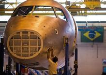 Un técnico trabaja en un avión en la línea de ensamblaje de Embraer, en Sao José dos Campos, 16 de octubre de 2014. La producción industrial de Brasil subió un 1,1 por ciento en junio respecto al mes previo, indicó el martes un reporte de la agencia de estadísticas del Gobierno, IBGE. REUTERS/Roosevelt Cassio