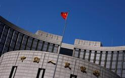 A Chinese national flag flutters outside the headquarters of the People's Bank of China, the Chinese central bank, in Beijing, April 3, 2014.   REUTERS/Petar Kujundzic/File Photo