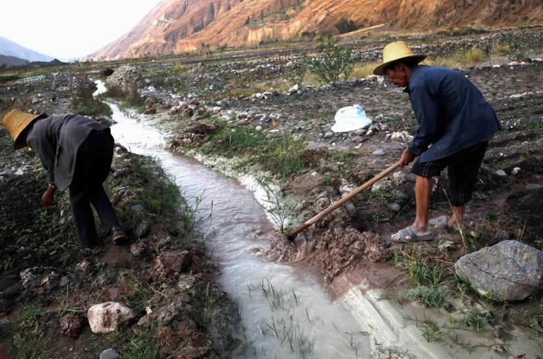 Farmers dig ditches to lead water from a white polluted stream into farm fields, in Dongchuan district of Kunming, Yunnan province, March 21, 2013.  REUTERS/Stringer