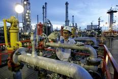 Рабочий проверяет трубы нефтепровода в Бангкоке. Цены на нефть снизились во вторник на фоне продолжительных беспокойств о перенасыщении мировых рынков, а также поскольку инвесторы зафиксировали прибыль после роста котировок почти на 3 процента в предыдущую сессию.  REUTERS/Sukree Sukplang/File Photo