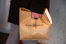 A customer holds a bag full of food inside of a Shake Shack store in New York January 30, 2015.  REUTERS/Lucas Jackson