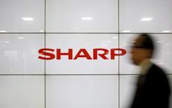A man walks past Sharp Corp's liquid crystal display monitors showing the company logo in Tokyo, Japan, February 25, 2016. REUTERS/Yuya Shino
