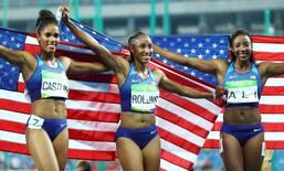 2016 Rio Olympics - Athletics - Final - Women's 100m Hurdles Final - Olympic Stadium - Rio de Janeiro, Brazil - 17/08/2016. Gold medallist Brianna Rollins (USA) of USA (C), silver medallist Nia Ali (USA) of USA (R) and bronze medallist Kristi Castlin (USA) of USA (L) hold up the U.S. flag.  REUTERS/Lucy Nicholson