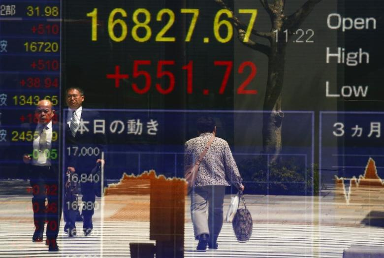 People are reflected in a screen displaying the Nikkei average outside a brokerage in Tokyo, Japan April 19, 2016. Japan's Nikkei share average soared on Tuesday morning, as a weak yen and a bounce in oil prices helped the market erase a sharp drop from the previous day.   REUTERS/Thomas Peter