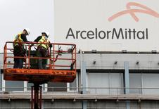 Workers stand near the logo of ArcelorMittal, the world's largest producer of steel, at the steel plant in Ghent, Belgium, July 7, 2016. REUTERS/Francois Lenoir - RTSHL7F