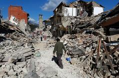 Человек идет среди обломков зданий, разрушенных землетрясением в центре Италии. Пескара Дель Тронто, 24 августа 2016 года. По меньшей мере 38 человек погибли в результате мощного землетрясения, произошедшего минувшей ночью. REUTERS/Remo Casilli