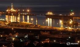 Нефтяная вышка в гавани Кейптауна 6 августа 2011 года. Цены на нефть снизились в ходе торгов среды, поскольку доллар удерживался вблизи трехнедельных максимумов, а статистика указала на рост запасов черного золота в США. REUTERS/Mike Hutchings/File Photo