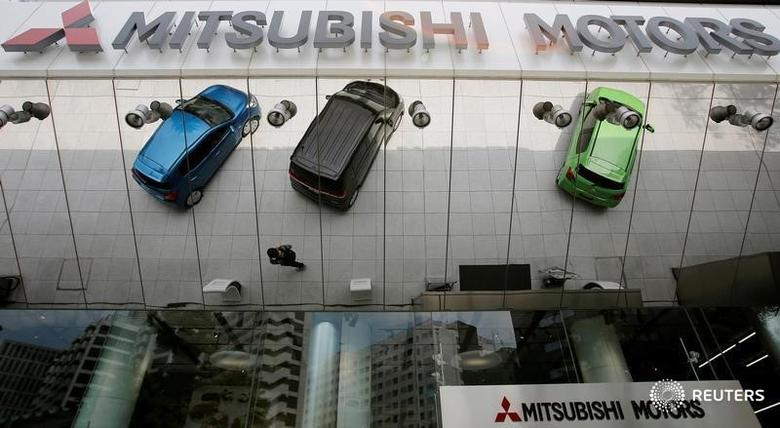 Mitsubishi Motors Corp's vehicles and a passer-by are reflected on an external wall at the company headquarters in Tokyo May 23, 2013. REUTERS/Toru Hanai/File Photo