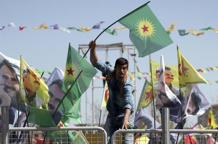 A demonstrator waves a flag of the outlawed Kurdistan Workers Party (PKK) during a gathering to celebrate the spring festival of Newroz in the Kurdish-dominated southeastern city of Diyarbakir, Turkey March 21, 2016. REUTERS/Sertac Kayar