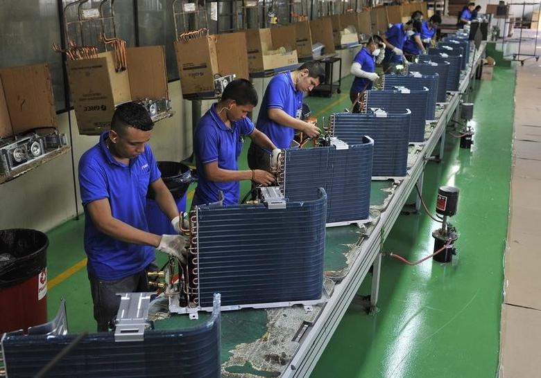 Employees work at a production line in a factory of the Chinese brand Gree, in Manaus June 24, 2014.  REUTERS/Jianan Yu