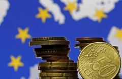 El Banco Central Europeo (BCE) mantendría su política monetaria sin cambios el 8 de septiembre y probablemente respondería a la presión de más alivio monetario anunciando una extensión de su programa de compra de activos antes de que acabe el año, según indicó un sondeo de Reuters. En la imagen, monedas de euro delante de un mapa de la UE en una foto tomada en Zenica, 28 de mayo de 2015. REUTERS/Dado Ruvic