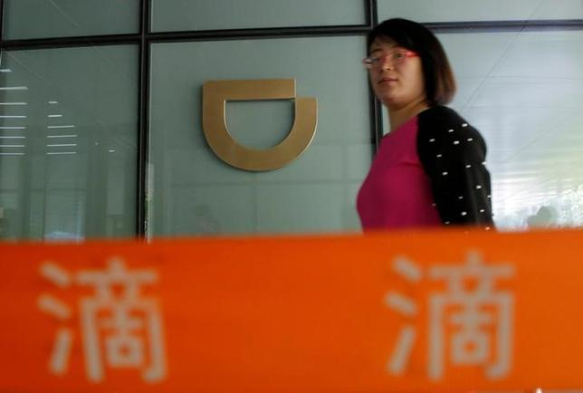 A woman walks past a sign of Didi Chuxing at its headquarters building in Beijing, China, May 18, 2016. REUTERS/Kim Kyung-Hoon/Files