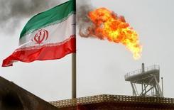 En la imagen de archivo se aprecia una llamarada en una plataforma de producción de petróleo junto a la bandera iraní, en el Golfo Pérsico. Irán está listo para respaldar cualquier decisión para ayudar a restaurar el equilibrio del mercado petrolero después de que recupere la participación de mercado que tenía antes de recibir sanciones internacionales, informó el sábado la agencia de noticias SHANA del Ministerio del Petróleo iraní. REUTERS/Raheb Homavandi/File Photo