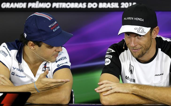 McLaren Formula One driver Jenson Button (R) of Britain listens to to Williams Formula One driver Felipe Massa of Brazil during a news conference for the Brazil F1 Grand Prix in Sao Paulo, Brazil, November 12, 2015. REUTERS/Paulo Whitaker/Files