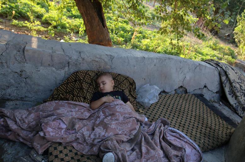 A boy sleeps outdoors in the rebel-held al-Sheikh Said neighbourhood of Aleppo, Syria September 1, 2016. REUTERS/Abdalrhman Ismail