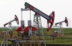 Станки-качалки на Бузовьязовском нефтяном месторождении в Башкортостане. 11 июля 2015 года. Цены на нефть немного снизились в понедельник, отдав набранное на предыдущей сессии 3-процентное преимущество, в то время как доллар вырос, а трейдеры сохраняли опасения о глобальном перенасыщении рынка, несмотря на признаки того, что производители могут попытаться бороться с низкими ценами. REUTERS/Sergei Karpukhin/File Photo