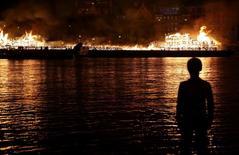 Menino observa réplica de 120 metros de Londres do século 17 pegando fogo à beira do Rio Tâmisa  para celebrar o Grande Incêncio de Londres de 1666 4/09/ 2016. REUTERS/Neil Hall