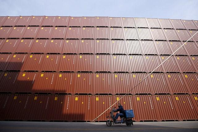 A man rides a vehicle past container boxes at a port in Shanghai, China, February 17, 2016. REUTERS/Aly Song/File Photo