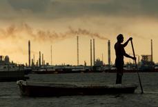 Рыбак на фоне НПЗ в Сингапуре 5 ноября 2013 года. Цены на нефть продолжили рост, поднявшись более чем на 1,5 процента в четверг, после того как данные отрасли указали на вероятность самого существенного недельного снижения запасов в США более чем за три десятилетия. REUTERS/Edgar Su/File Photo