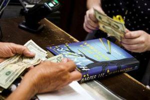 A customer purchases a copy of Harper Lee's book ''Go Set a Watchman'' at a Barnes & Noble store in New York, July 14, 2015.  REUTERS/Lucas Jackson/File Photo