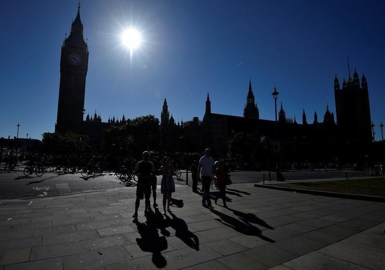 People walk past the Houses of Parliament and the Big Ben clock tower in London, Britain, August 23, 2016. REUTERS/Hannah McKay
