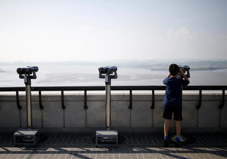A boy looks at a North Korean propaganda village through a pair of binoculars from an observatory platform near the demilitarized zone separating the two Koreas in Paju, South Korea, September 9, 2016. REUTERS/Kim Hong-Ji