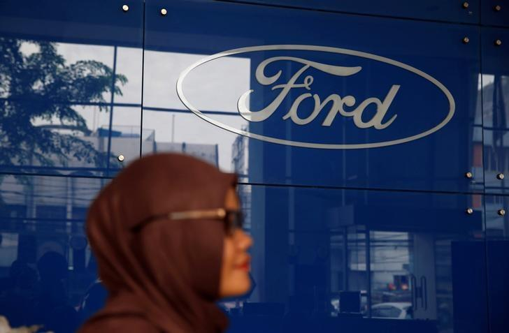 A woman stands near a Ford logo at Central Jakarta Ford Dealer in Jakarta, Indonesia, June 27, 2016. REUTERS/Beawiharta/Files