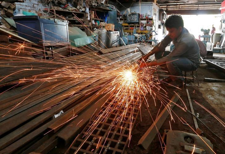A worker grinds a metal gate inside a household furniture manufacturing factory in Ahmedabad, July 1, 2016. REUTERS/Amit Dave/Files