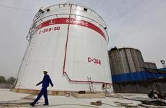 Foto de archivo de un trabajador caminando cerca de un estanque de petróleo, en la refinería de Sinopec en Wuhan, China. 25 de abril de 2012. El bombeo de petróleo de China se redujo casi un 10 por ciento en agosto frente al mismo mes del año previo, a su menor nivel en más de seis años, mostraron datos de la oficina de estadísticas, en momentos en que la debilidad de los precios sigue afectando a los principales productores. REUTERS/Stringer/File Photo