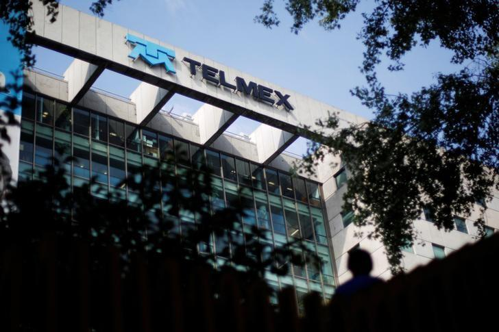 A man crosses a pedestrian bridge next to the headquarters of internet and fixed-line phone company Telmex, commercial brand of America Movil, in Mexico City July 9, 2014. REUTERS/Bernardo Montoya/File Photo