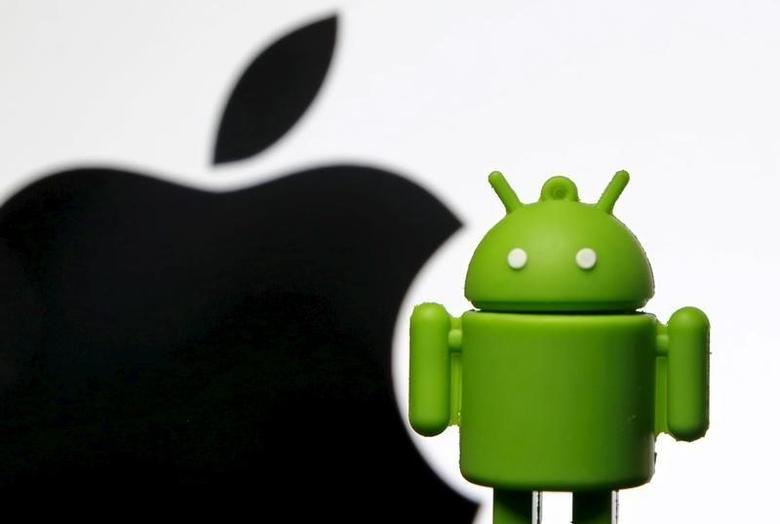 An Android mascot is seen in front of a displayed logo of Apple in this photo illustration taken in Zenica, Bosnia and Herzegovina, May 5, 2015. REUTERS/Dado Ruvic