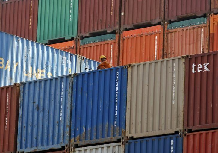 A worker sits on a ship carrying containers at Mundra Port, Gujarat April 1, 2014. REUTERS/Amit Dave/Files