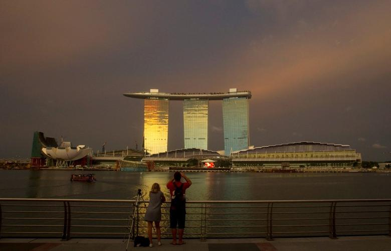 Tourists stand at a promenade across the water from the Marina Bay Sands integrated resort in Singapore June 22, 2010. REUTERS/Vivek Prakash/File Photo