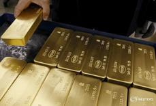 Сотрудник Красцветмета держит в руках слиток золота в Красноярске 5 июня 2015 года. Золотовалютные резервы РФ достигли значения $399,6 миллиарда, максимума с 12 декабря 2014 года, из-за переоценки валют и активов, входящих в структуру резервов, а также благодаря положительному балансу операций валютного репо Центробанка с локальными банками. REUTERS/Ilya Naymushin