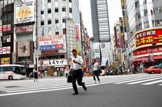 Una persona revisando su teléfono móvil en una calle en el distrito comercial de Tokio, sep 8, 2016. Apple Inc y Google de Alphabet Inc realizaron prácticas que perjudicaron la libre competencia en el mercado de las aplicaciones para telefonía móvil, dijo el jueves un panel asesor al Ministerio de Economía, Comercio e Industria de Japón.   REUTERS/Kim Kyung-Hoon