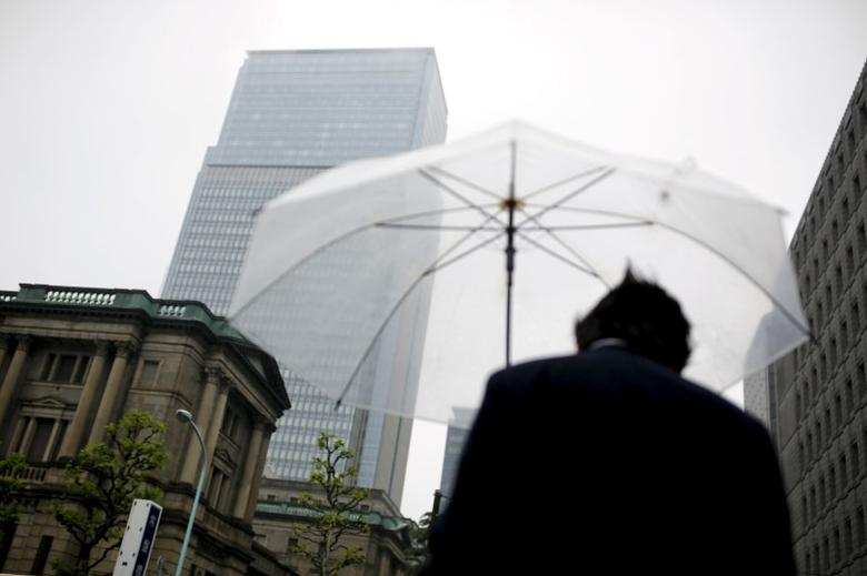 A businessman holds an umbrella as he stands near the Bank of Japan headquarters in Tokyo, Japan, April 28, 2016. REUTERS/Thomas Peter/File Photo