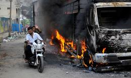 Men ride a motorcycle past a lorry in Bengaluru, which was set on fire by protesters after India's Supreme Court ordered Karnataka state to release 12,000 cubic feet of water per second every day from the Cauvery river to neighbouring Tamil Nadu, India September 12, 2016. REUTERS/Abhishek N. Chinnappa