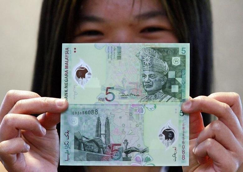 一名马来西亚女子展示一张马币现钞正反面。REUTERS/Bazuki Muhammad