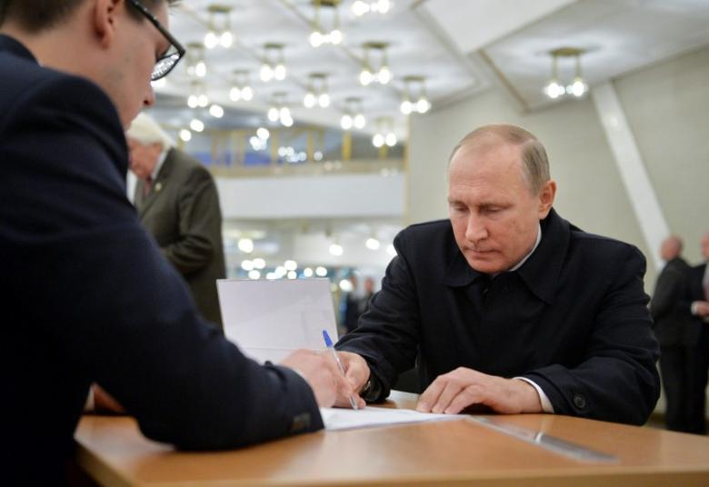 Russian President Vladimir Putin signs a document before getting a ballot at a polling station during a parliamentary election in Moscow, Russia, September 18, 2016. Sputnik/Kremlin/Alexei Druzhinin via REUTERS