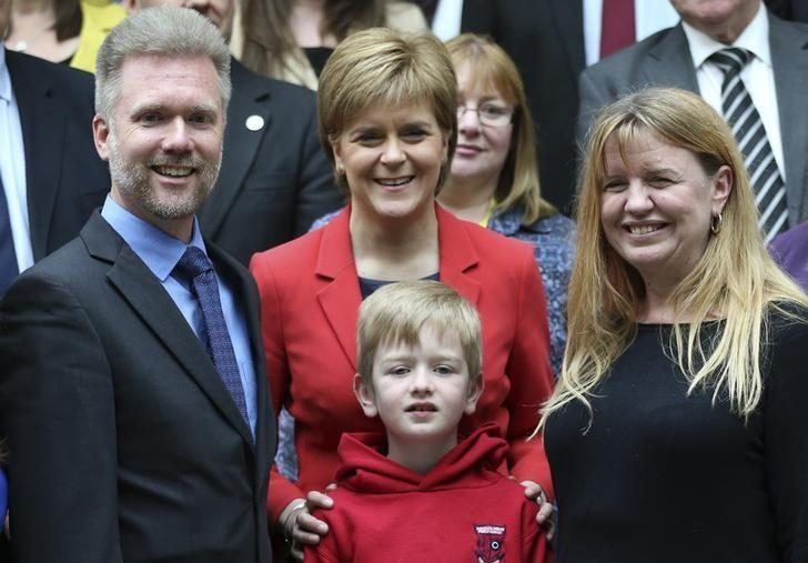 Gregg (L) Kathryn (R) and Lachlan Brain pose for photographers with Scotland's First Minister Nicola Sturgeon in Scotland's devolved Parliament in Edinburgh, Scotland, May 26, 2016.  REUTERS/Russell Cheyne/File Photo